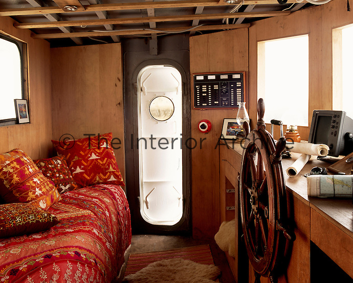 A tiny guest room is situated on the bridge amongst  maritime charts and the wheel