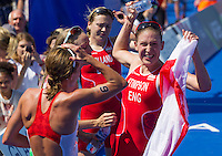 24 JUL 2014 - GLASGOW, GBR - Jodie Stimpson (ENG) (right) from England celebrates winning the first gold medal of the 2014 Commonwealth Games at the women's  triathlon in Strathclyde Country Park, in Glasgow, Scotland watched by silver medalist Kirsten Sweetland (CAN) (left) from Canada, Aileen Reid (NIR) (second from the left) from Northern Ireland and England team mate, bronze medalist Vicky Holland (ENG) (third from the left) (PHOTO COPYRIGHT &copy; 2014 NIGEL FARROW, ALL RIGHTS RESERVED)<br /> *******************************<br /> COMMONWEALTH GAMES <br /> FEDERATION USAGE <br /> RULES APPLY<br /> *******************************