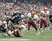 Washington Redskins right defensive end Dexter Manley (72) sacks Los Angeles Raiders quarterback Jim Plunkett (16) during their game at RFK Stadium in Washington, D.C. on October 2, 1983.  Trailing Manley on the play are right linebacker Rich Milot (57) and left defensive tackle Dave Butz (65).<br /> Credit: Howard L. Sachs / CNP