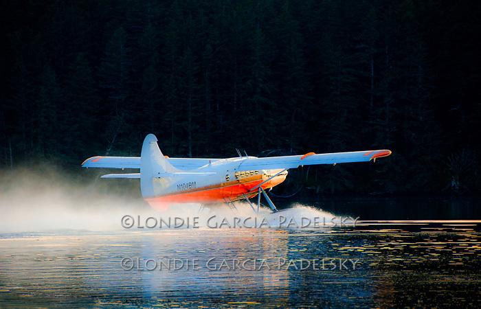 Float plane takes off at sunset from Neketa Bay at Shuyak Island. Shuyak Island State Park, Alaska