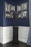 Architectural prints of classical ornamentation hang on the walls behind a Greecian head  in a corner of the reception room
