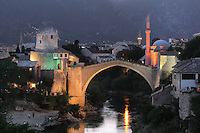 Stari Most or Old Bridge at night, a 16th century Ottoman bridge across the Neretva river, and the Koski Mehmed Pasha Mosque, in Mostar, Bosnia and Herzegovina. The bridge was destroyed in the 1990s Yugoslavian war and has been rebuilt. The town is named after the mostari or bridge keepers of the Old Bridge. Mostar developed in the 15th and 16th centuries as an Ottoman frontier town and is listed as a UNESCO World Heritage Site. Picture by Manuel Cohen