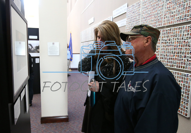 Amy Roby, project manager of the Always Lost: A Meditation on War exhibit, and Vietnam Veteran Bruce Bertram look at a photo in the exhibit at the Legislative Building in Carson City, Nev., on Monday, April 6, 2015. <br />