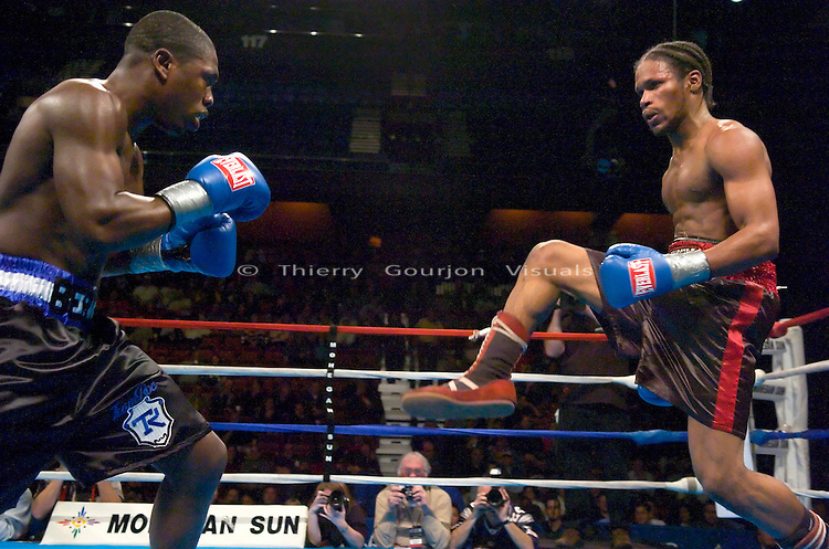 Andre Berto (black and blue) and Joseph Benjamin  in the ring during their Junior Middleweight fight at the Mohegan Sun Casino in Uncasville, CT on 01.21.05. Berto won by Unanimous Decision.<br />