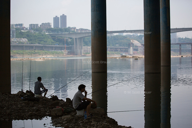 People gather and fish under the elevated Shabin Road near Ciqikou next to the Jialing River in the Shapingba District of Chongqing, China.