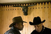 2 December 2006 - New York City, NY - Karl Washington (L), aka Comboy Wash, and Warren Smalls, aka Black Red, members of the Federation of Black Cowboys, talk after lunch at the Cedar Lanes stables in the borough of Queens in New York City, USA, 2 December 2006. The Federation gathers black men and women who recreate the heritage of black cowboys, teach kids to ride and put on 'rodeo showdeos'.