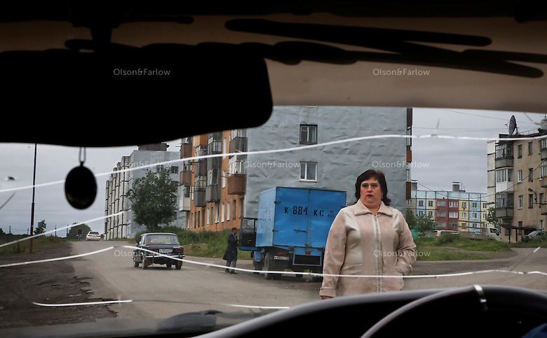 Drab street scene through cracked windshield in remote Soviet town.