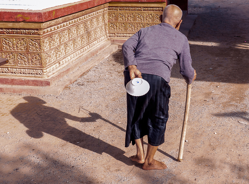 A old nun walking through the monastery Activities and way of life, around and near the Tonle Sap Lake, Siem Reap area, Cambodia