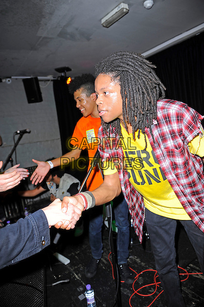 Solomon Radke &amp; Dee Radke of Radkey <br /> performing in concert, The Blackeart, Camden, London, England. <br /> 17th October 2013<br /> on stage in concert live gig performance performing music full length red check shirt yellow top shaking hands profile <br /> CAP/MAR<br /> &copy; Martin Harris/Capital Pictures