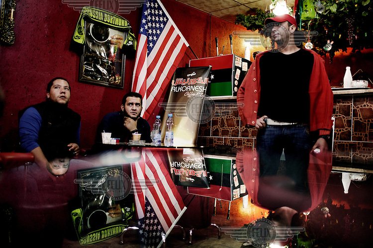 A glass table reflects three young men and an American flag in a Benghazi cafe, watching a football game and sipping coffee. On 17 February 2011 Libya saw the beginnings of a revolution against the 41 year regime of Col Muammar Gaddafi..