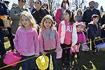 North Merrick, New York, USA. March 31, 2018. Young girls, many wearing pink, and boys wait behind yellow tape for start of traditional Easter Egg Hunt at the Annual Eggstravaganza, held at Fraser Park and hosted by North and Central Merrick Civic Association (NCMCA).