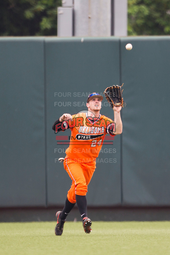 Oklahoma State Cowboys outfielder Conor Costello #24 makes a catch during the NCAA baseball game against the Texas Longhorns on April 26, 2014 at UFCU Disch–Falk Field in Austin, Texas. The Cowboys defeated the Longhorns 2-1. (Andrew Woolley/Four Seam Images)
