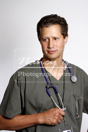 A male wearing scrubs and a stethoscope