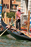 A gondolier guides his gondola on the Grand Canal in Venice, Italy
