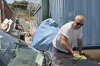 Palermo,man living in the house container after being evicted, washes his car.<br /> Palermo, abitante del campo containers allestito dal comune per famiglie sfrattate mentre lava la sua macchina.