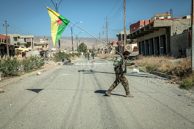 13/11/2015-- Iraq,Sinjar -- One of the YPG fighters holding the YPG flag, he was trying to put the flag in somewhere that everyone can see.