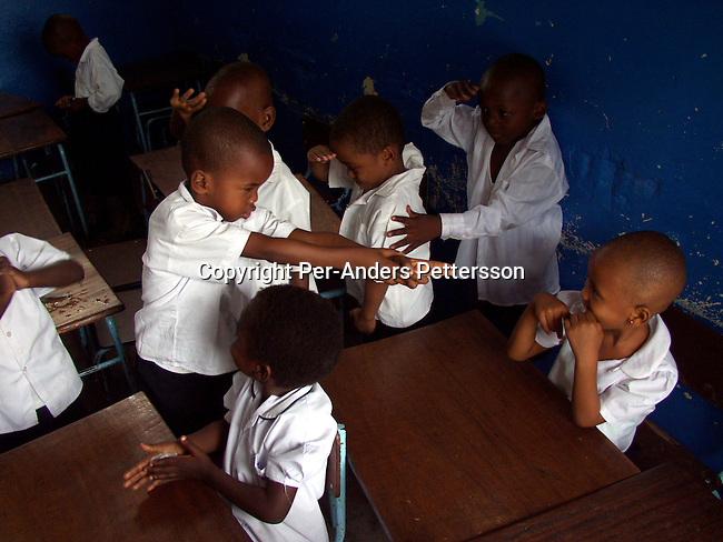 dicocon00131 .Country Congo Unidentified boys acting as soldiers during the singing of patriotic military song in their class on February 28, 2002 at ÒBambiniereÓ a school in Lingwala district, in Kinshasa, Congo. The teacher tells them about the occupation of Rwandan and Ugandan troops in the country..©Per-Anders Pettersson/iAfrika Photos