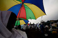 a pilgrim prays under the rain during the Saint john the baptist orthodox religious festival in Shankora, Ethiopia on Thursday July 06 2006.Tens of thousands of believers gather for the holy festival which is famous throughout the country for the holiness of its water. Many believe that the holy water of a nearby waterfall if drank during the festival can cure any disease, especially HIV AIDS. Preachers come from all over the country to try to persuade the ill not to take conventional medication, not to go to hospitals, but only to drink holy water and pray. the clash between traditional believes and modern medicine is a serious issue in Ethiopia.