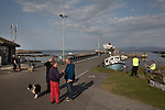 Islanders waiting for the arrival of the Caledonian MacBrayne ferry at Scalasaig from Oban on the the Inner Hebridean island of Colonsay on Scotland's west coast.  The island is in the council area of Argyll and Bute and has an area of 4,074 hectares (15.7 sq mi). Aligned on a south-west to north-east axis, it measures 8 miles (13 km) in length and reaches 3 miles (4.8 km) at its widest point, in 2019 it had a permanent population of 136 adults and children.