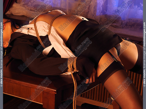 Sexy Japanese woman tied up with bondage ropes on a table