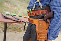 Competitor in period dress wearing his weapons attends the Cowboy Action Shooting European Championship in Dabas, Hungary on August 11, 2012. ATTILA VOLGYI
