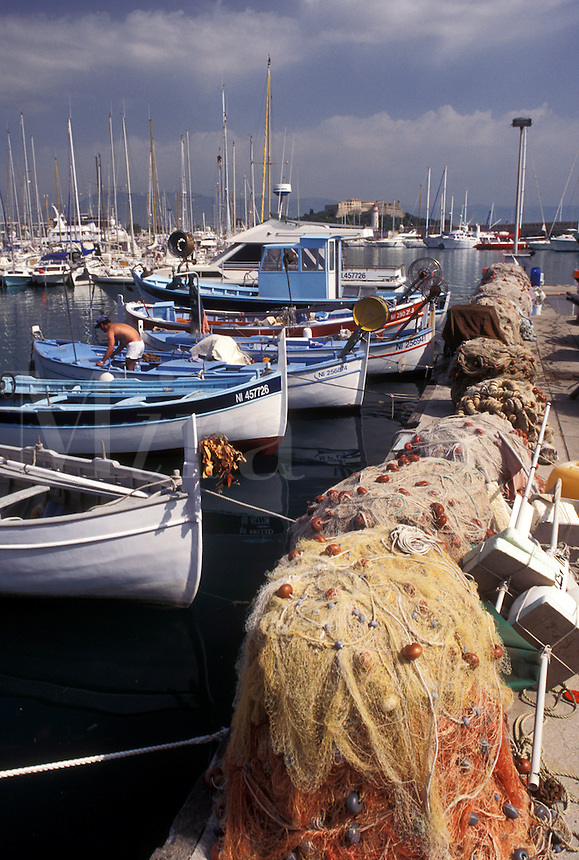 fishing boats, Antibes, Cote d' Azur, France, Provence, Alpes-Maritimes, Europe, Fishing boats docked in Port Vauban Harbor on the Mediterranean Sea in the city of Antibes. Fishing nets piled on the dock.