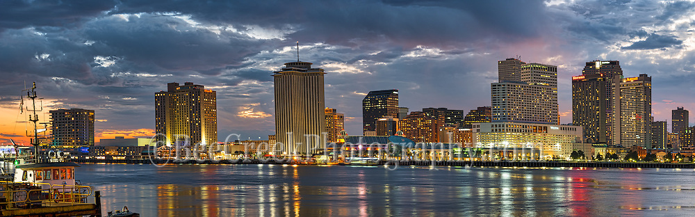 We capture this New Orleans skyline in downtown area around dusk as the high rise building light came on and it created this nice reflections in the Mississippi River. There was stil a little color in the sky from the sunset just enough to gve it some pop over the cityscape with some oranges and pinks mingle with the dark clouds. This  New Orlean skyline pano was taken from across the Mississippi River at dusk.  The view of the city high rise buildings along the shore line makes for a nice image as the building reflect in the water shortly after sunset. New Orleans is the largest city in the state of Louisiana population of around 1.5 million people. The city attract tourist from all over the world with its many popular neighborhoods such as the famous French Quarters, Jackson Square and many more area of interest. Beside Bourbon street and french quarter there are plenty of wonderful restaurants in the area. New Orleans also has a lot of things to do such as World War Museum, Art Museums, Aquarium, or even a visit to the city cementaries, plus you can enjoy a visit to the Superdome home of the New Orleans Saints. There are riverboats rides along the Mississippi River just some of the thing available to do in the city.