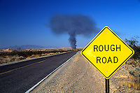 """Rough Road"" ahead, yellow highway sign in front of mushroom shaped smoke cloud on road in western US..Concept: ""trouble ahead""."