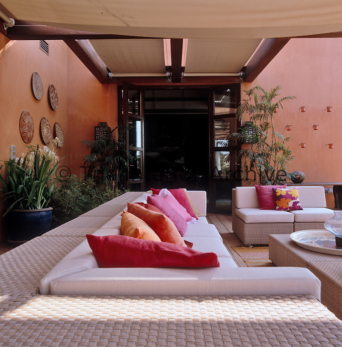 Large comfortable sofas and armchairs made of synthetic rattan are situated under the shade of canvas awnings
