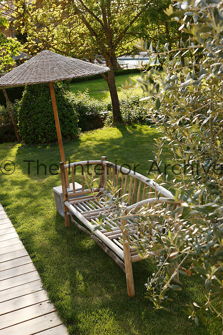 Beside a decking walkway in the garden a rustic bench is shaded by a rattan umbrella