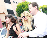 US actress Lindsay Lohan (center) with an unknown model (left) and her bodyguard (right) in Los Angeles, California 09 May 2008. The actress is doing a photo shoot for her new leggings line on Robertson Boulevard and wanted the paparazzi to join her.