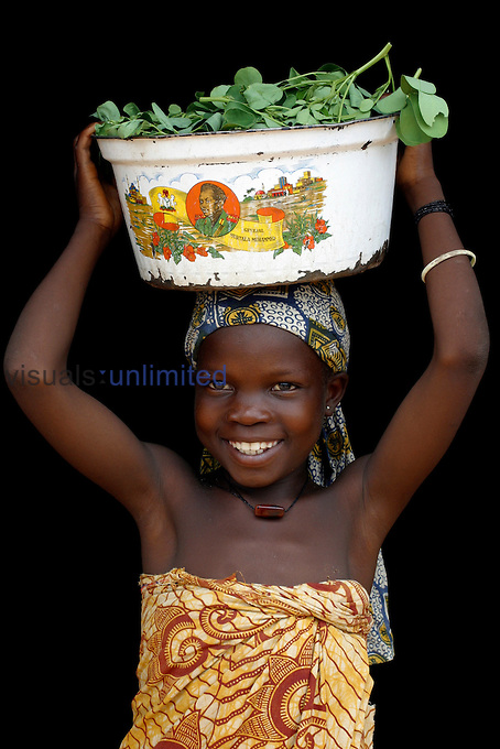 Girl carrying greens in a metal pan on her head, Lagos, Nigeria