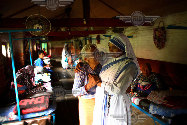 A sister from Mother Teresa's Missionaries of Charity comforts an elderly resident in the Pashupati Bridhashram (old peoples' home). Part of the Pashupatinath Temple complex, the old peoples' home is the largest of its type in Kathmandu, home to 140 women and 90 men. Nepal has a steadily growing elderly population.