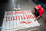 Apr. 30 - BANGKOK, THAILAND: A Red Shirt writes out anti-government graffiti in chili peppers on a street in Bangkok Friday. The Red Shirts moved one of their barricades in the Sala Daeng Intersection in Bangkok Friday In one of the first positive moves to take place since the Red Shirts occupied central Bangkok in early April. The barricade was moved far enough back to open one lane of traffic on  Ratchadamri Street to allow ambulance access to King Chulalongkorn Memorial Hospital, a large hospital at the intersection. Many of the patients in the hospital have been moved to other hospitals because a group of Red Shirts entered the hospital Thursday looking for Thai security personnel, who were not in the hospital. The stand off between the Red Shirts and the government enters its third month in May. The Red Shirts continue to call for Thai Prime Minister Abhisit Vejjajiva to step down and dissolve parliament and demand the return of ousted Prime Minister Thaksin Shinawatra.   PHOTO BY JACK KURTZ