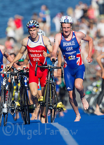 25 AUG 2013 - STOCKHOLM, SWE - Alistair Brownlee (GBR) (right, in blue, white and red) of Great Britain leaves transition at the start of the bike during the men's ITU 2013 World Triathlon Series round  in Gamla Stan, Stockholm, Sweden (PHOTO COPYRIGHT © 2013 NIGEL FARROW, ALL RIGHTS RESERVED)