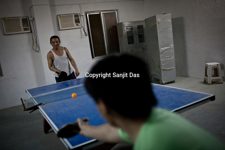 Chinese workers take a break and play ping-pong at the Chinese Colony in the Adani Power plant in Mundra port industrial city of Gujarat, India. Indian power companies have handed out dozens of major contracts to Chinese firms since 2008. Adani Power Ltd have built elaborate Chinatowns to accommodate Chinese workers, complete with Chinese chefs, ping pong tables and Chinese television. Chinese companies now supply equipment for about 25% of the 80,000 megawatts in new capacity.