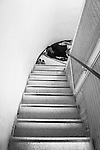 A man tries to find some sleep in the staircase. Every square foot was used, such was the number of people occupying the building.