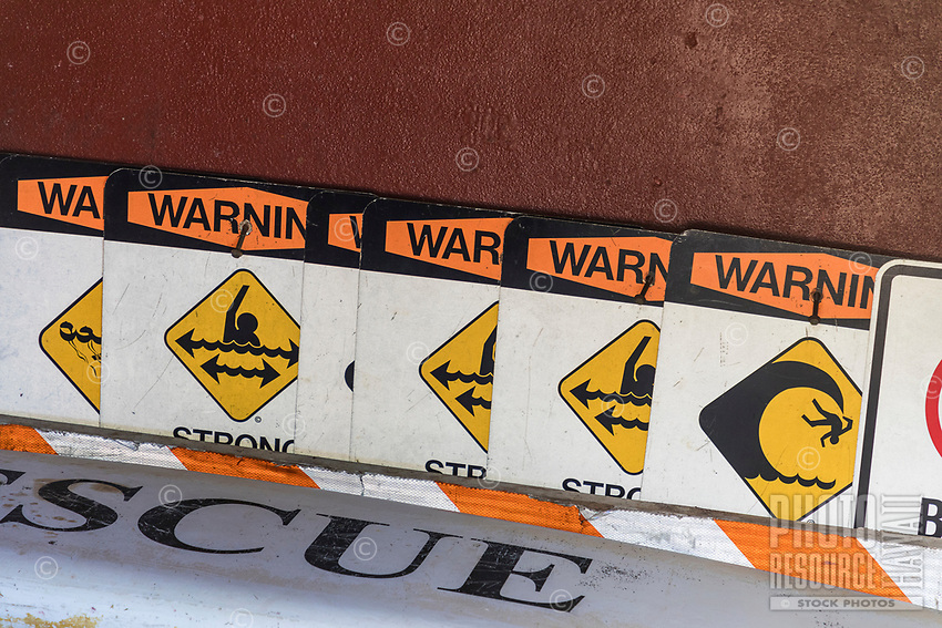 A variety of safety signs ready to post at Honoli'i Beach Park, Big Island.