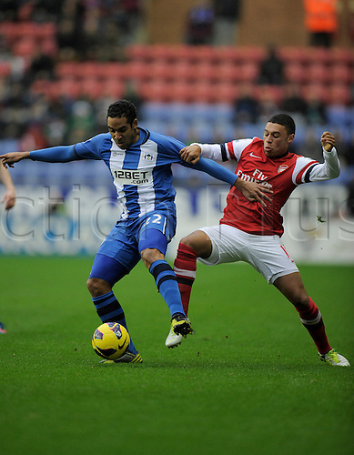 22.12.2012 Wigan, England. Jean Beausejour of Wigan and Alex Oxlade-Chamberlain of Arsenal  in action during the Premier League game between Wigan Athletic and Arsenal at the DW Stadium.
