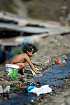 A Roma girl collects drinking water from a dirty stream flowing through the Maxsuda neighborhood of Varna, Bulgaria.