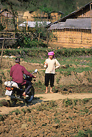 Minsk motorcycle and rider approaches flower Hmong girl on trail,, Northern Vietnam