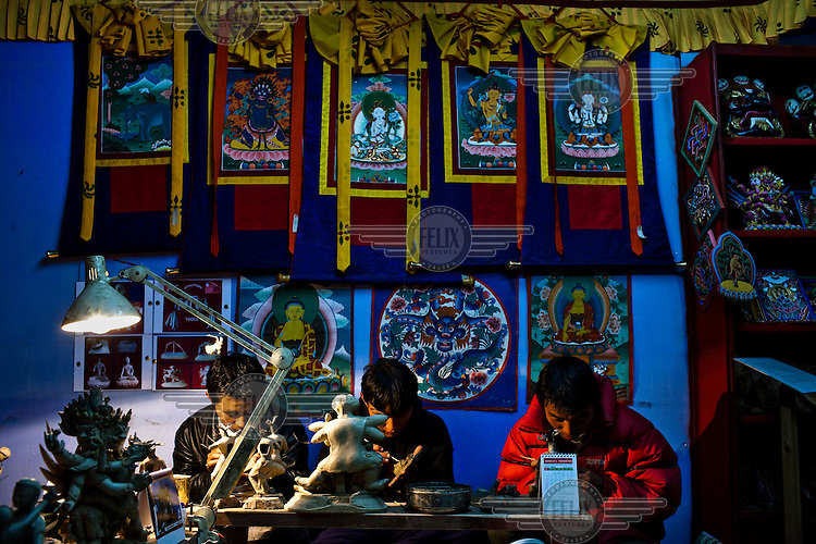 Local Bhutanese Craftsmen work in a handicrafts store in the capital Thimpu.