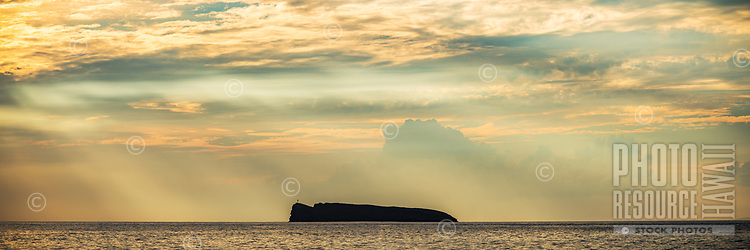 Sun rays beam down over Molokini Crater off the western coast of Maui.