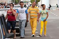 Cuba, Cienfuegos.  Four Pedestrians in Sporty Casual Clothing