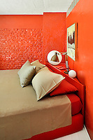 A modern bedroom with vibrant red painted brick walls. A double bed is placed at a slight angle in the corner with an angle-poise lamp on a shelf behind. The bed linen is in red and neutral.