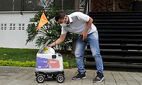 MEDELLÍN, COLOMBIA-APRIL 24: A customer receives an order from the robots used to deliver food during the new Coronavirus pandemic, COVID-19. on April 24, 2020, in Medellín, Colombia. The launch of Colombian on-demand services Rappi is using robots on wheels designed by KiwiBot as a way to bring food to people who were forced to stay home during childbirth as a preventive measure to stop the spread of COVID-19 (Photo from Fredy Builes / VIEWpress via Getty Images).
