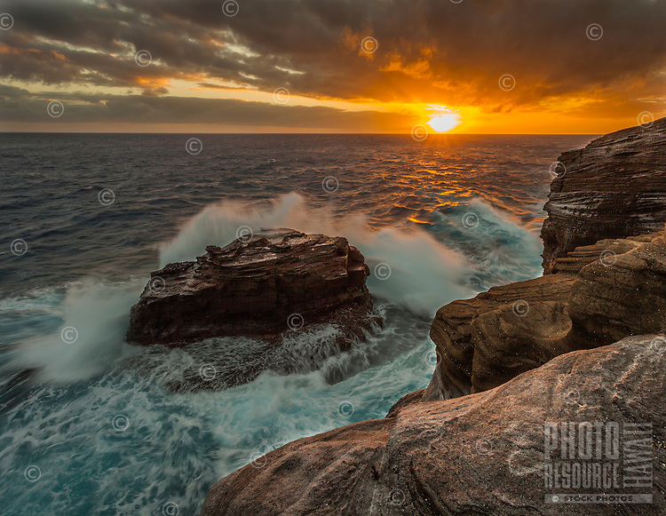 Waves backlit by the sunset crash into the cliffs along the Ka'iwi coast of O'ahu.