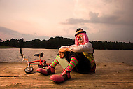 A clown sits on a pier with his miniature bicycle and a book.