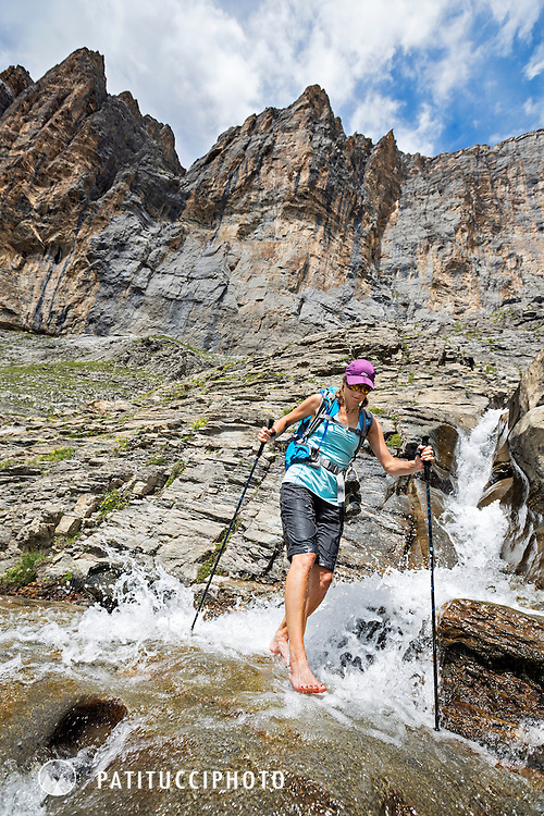 One woman crossing a small creek while hiking on the Silberhorn Hut Trail, an alpine trail with some very unique sections of wide open, rocky landscapes and extremely exposed. Jungfrau Region, from Lauterbrunnen Valley, Switzerland