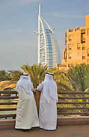 Dubai. Two men look out over the Madinat Jumeirah towards the Burj al Arab Hotel..